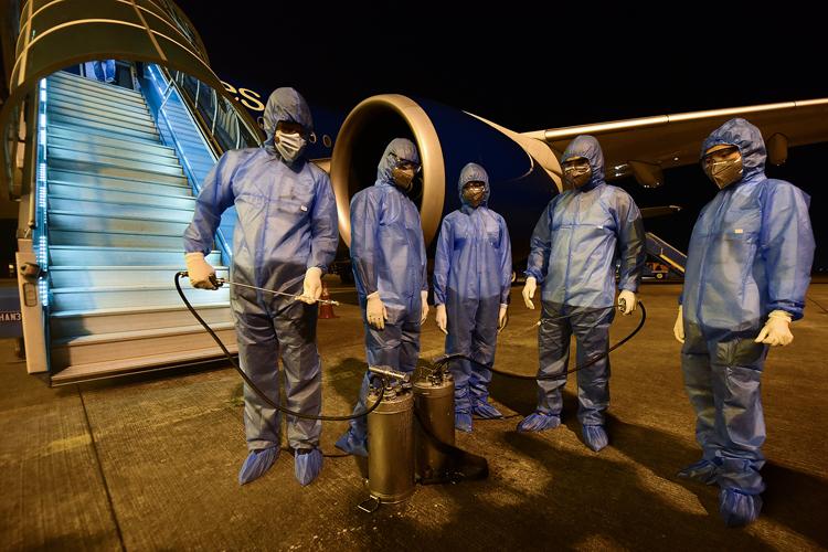 Các nhân viên y tế khử trùng một máy bay tại Hà Nam hồi tháng 3/2020. Ảnh: Giang Huy.