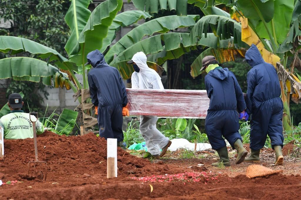 Nhóm người đào mộ hạ huyệt một quan tài ở nghĩa trang Pondok Ranggon, thủ đô Jakarta hôm 6/5. Ảnh: AFP.