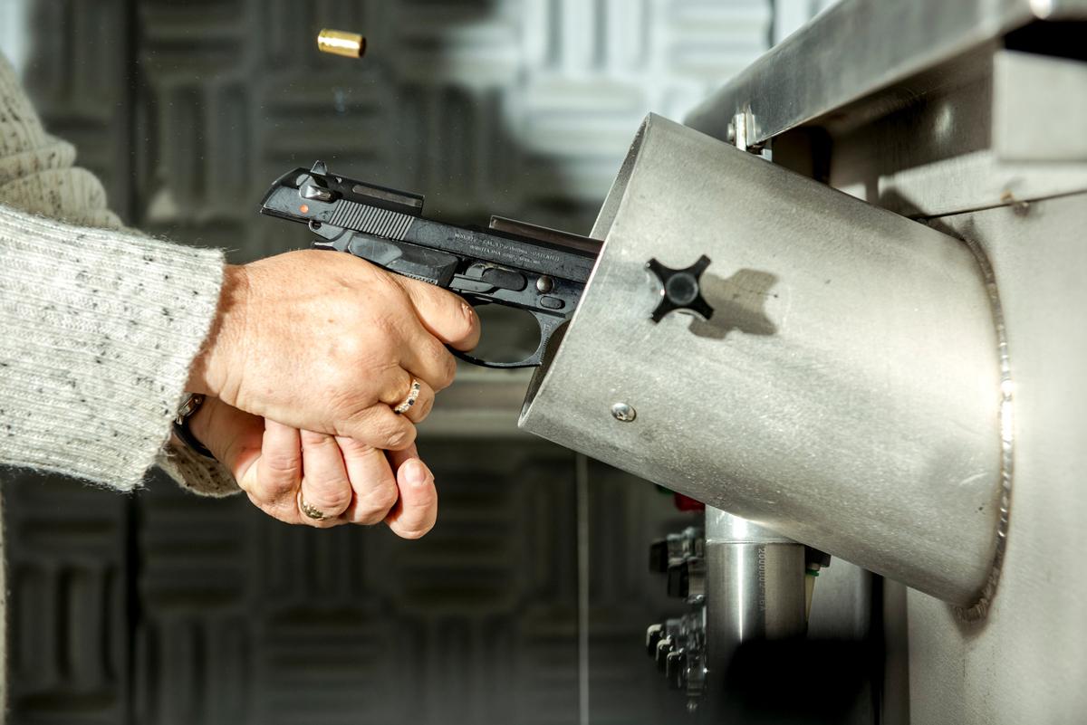 Chuyên gia bắn súng vào thùng nước chuyên dụng để lấy mẫu viên đạn từ khẩu súng khả nghi. Ảnh: New York Times.