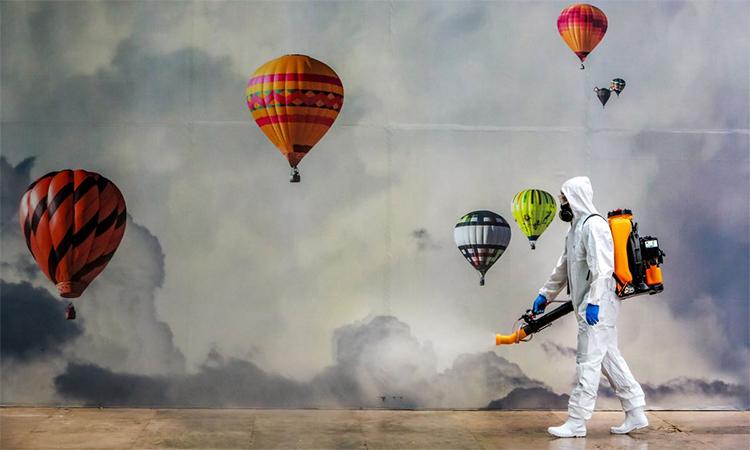 Nhân viên y tế mặc trang phục bảo hộ phun hóa chất tẩy trùng tại một trung tâm thương mại ở Caxias do Sul, Brazil, ngày 13/5. Ảnh: AFP.