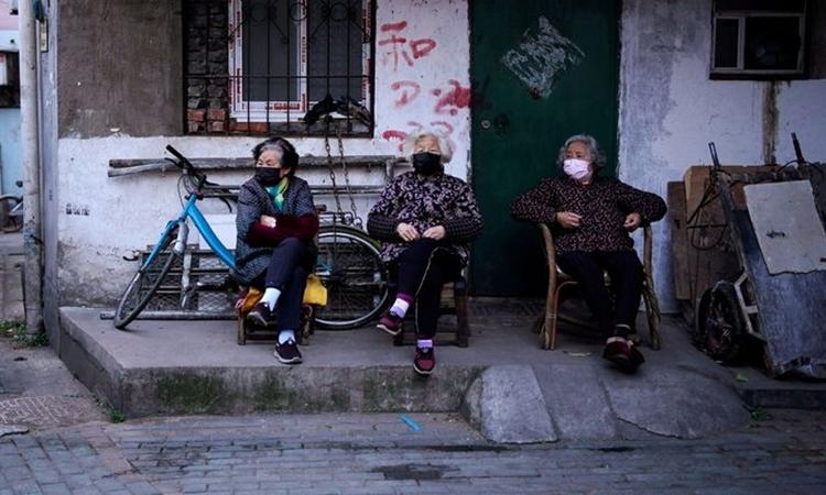 Người dân đeo khẩu trang phòng nCoV tại một khu dân cư ở Vũ Hán hôm 12/4. Ảnh: Reuters.