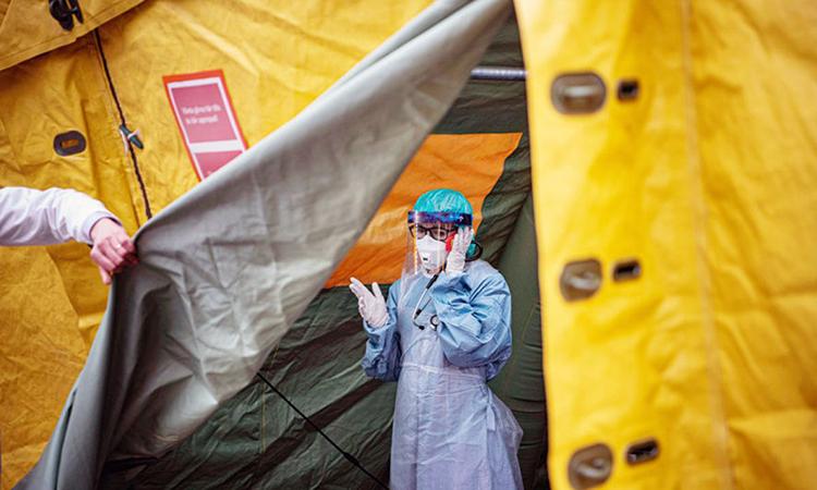Nhân viên y tế đứng tại lều xét nghiệm và tiếp nhận người nghi nhiễm nCoV tạiStockholm hồi tháng 4. Ảnh: AFP.