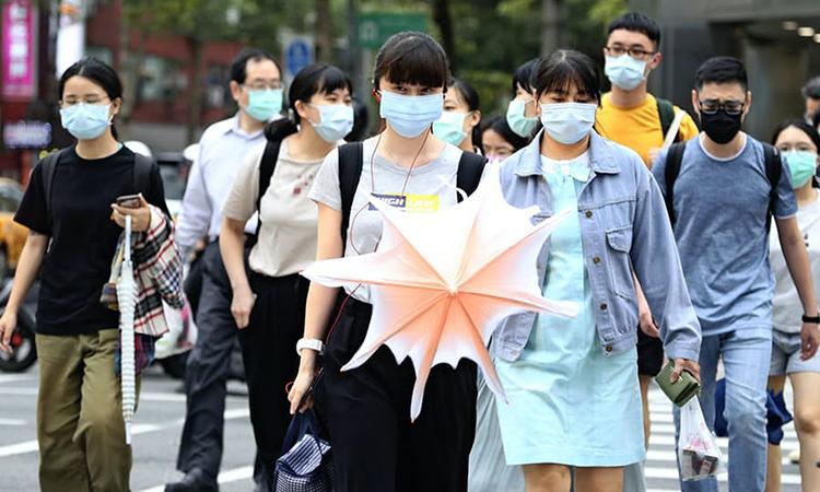 Người dân Đài Loan đeo khẩu trang đi trên phố Đài Bắc hôm 18/5. Ảnh: AP.