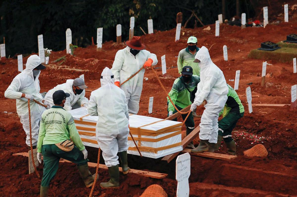Các nhân viên nghĩa trang chôn cất một bệnh nhân Covid-19 ở thủ đô Jakarta, Indonesia, hôm 22/4. Ảnh: Reuters