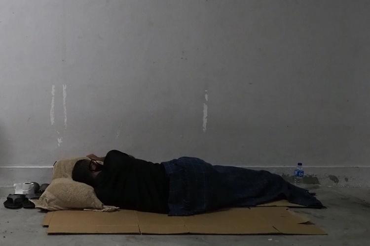 Jason, 37 tuổi, ngủ trên tấm bìa cứng dưới nhà ga tàu điện ngầm. Ảnh: Today Online.