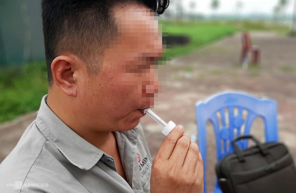 Tài xế container kiểm tra nhanh ma tuý qua ống thổi nước bọt trên Quốc lộ 17 qua huyện Thuận Thành, Bắc Ninh sáng 19/5. Ảnh: Bá Đô