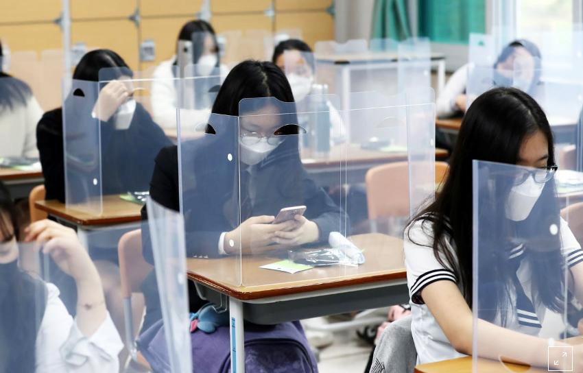Học sinh trung học đeo khẩu trang, ngồi sau tấm chắn giọt bắn trong ngày đầu đi học 20/5 tại thành phố Daejeon, Hàn Quốc. Ảnh: Yonhap.