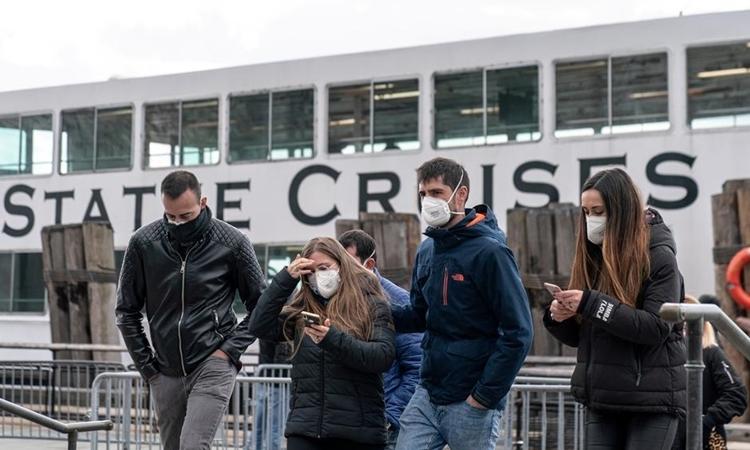 Người dân Mỹ đeo khẩu trang khi đi trên đường phố hôm 16/3. Ảnh: Reuters.