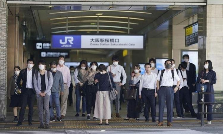 Người dân Nhật Bản đứng chờ ở nhà ga Osaka hôm 21/5. Ảnh: Reuters.