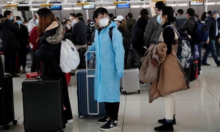 Hành khách Trung Quốc đợi làm thủ tục tại sân bay quốc tế JFK, New York, Mỹ ngày 13/3. Ảnh: Reuters.