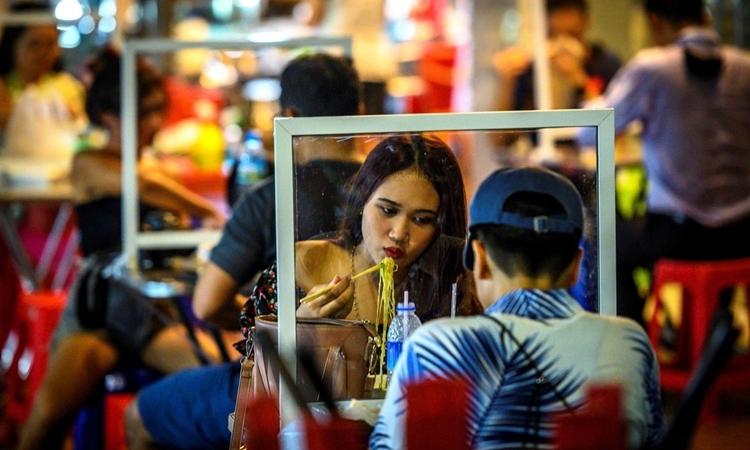 Người dân Thái Lan ngồi ăn tại một nhà hàng có vách ngăn ở Chinatown, Bangkok, hôm 21/5. Ảnh: AFP.