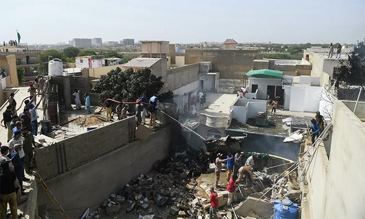 Lực lượng cứu hộ xịt nước vào mảnh vỡ của chiếc máy bay lao xuống khu dân cư ở Karachi, Pakistan, ngày 22/5. Ảnh: AFP.