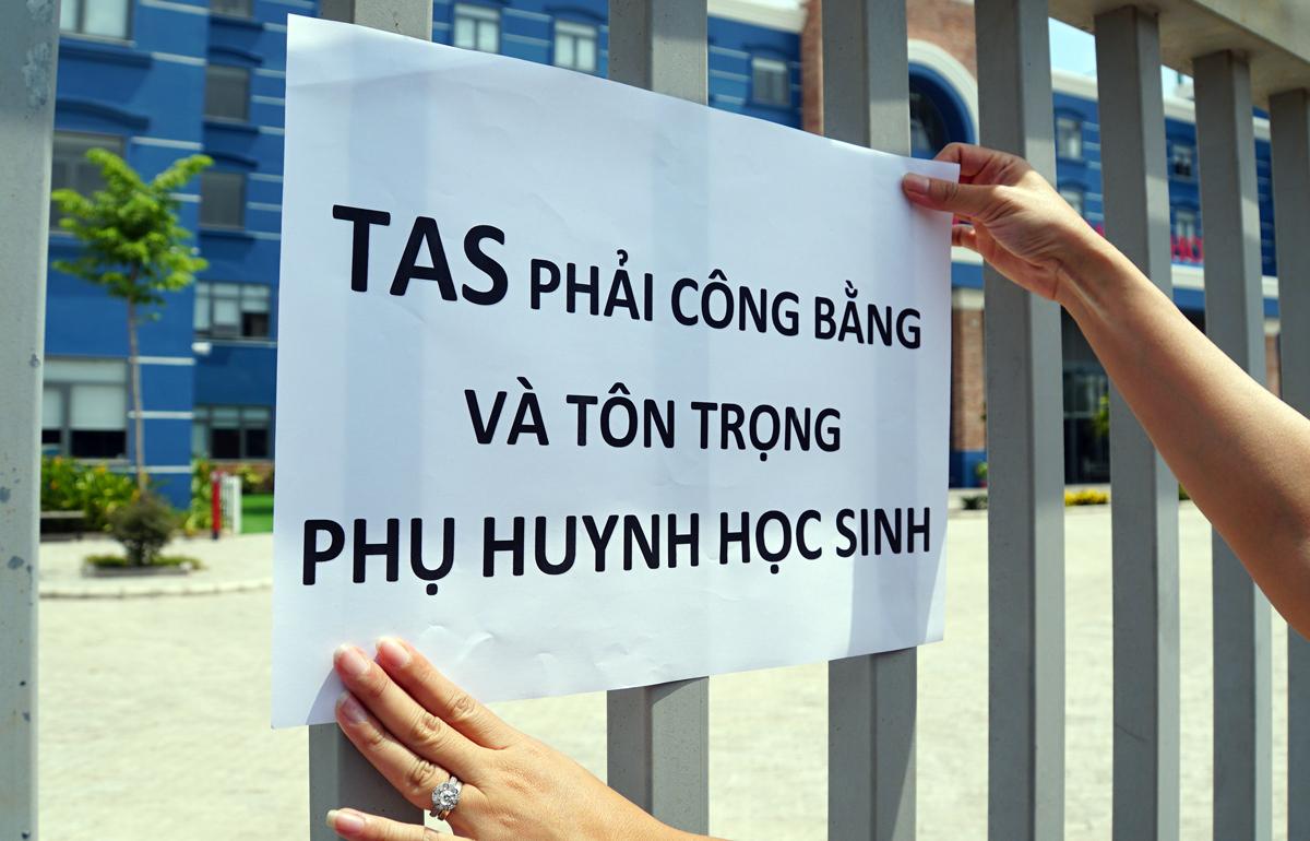 Phụ huynh trường Quốc tế Mỹ (TAS) mang biểu ngữ yêu cầu trường đối thoại giải quyết thu học phí trong ngày nghỉ chống Covid-19, chiều 11/5. Ảnh: Mạnh Tùng.