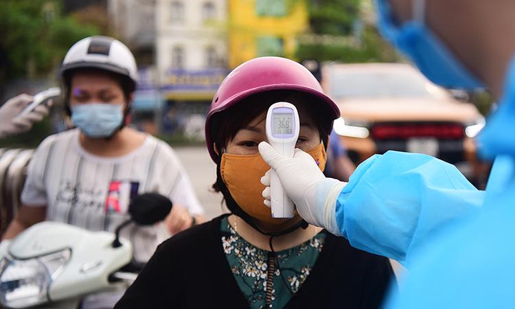 Nhân viên y tế tiến hành đo thân nhiệt tại Bệnh viện Bạch Mai, Hà Nội, ngày 28/3. Ảnh: Giang Huy.
