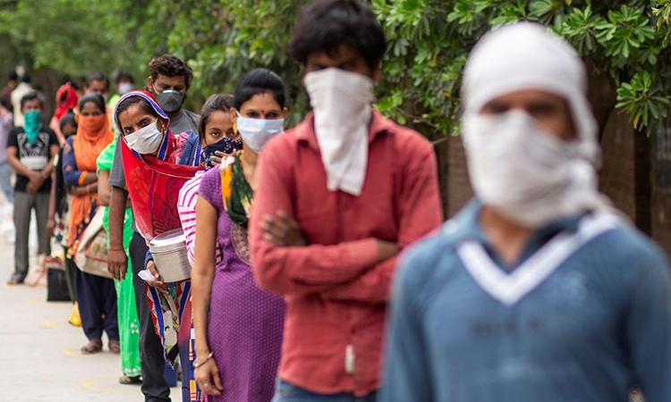 Người Ấn Độ xếp hàng chờ nhận thực phẩm miễn phí tại một khu công nghiệp ở New Delhi, hôm 23/4. Ảnh: Reuters.