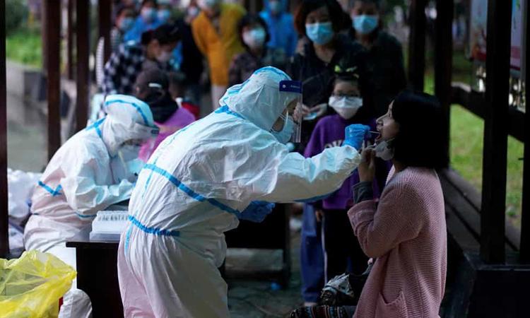Nhân viên y tế lấy mẫu xét nghiệm nCoV tại một khu dân cư ở thành phố Vũ Hán, Trung Quốc hôm 14/5. Ảnh: Reuters.