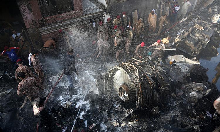 Binh sĩ và nhân viên cứu hộ Pakistan tìm kiếm nạn nhân gần động cơ của chiếc Airbus A320 gặp nạn ở Karachi, ngày 22/5. Ảnh: AFP.