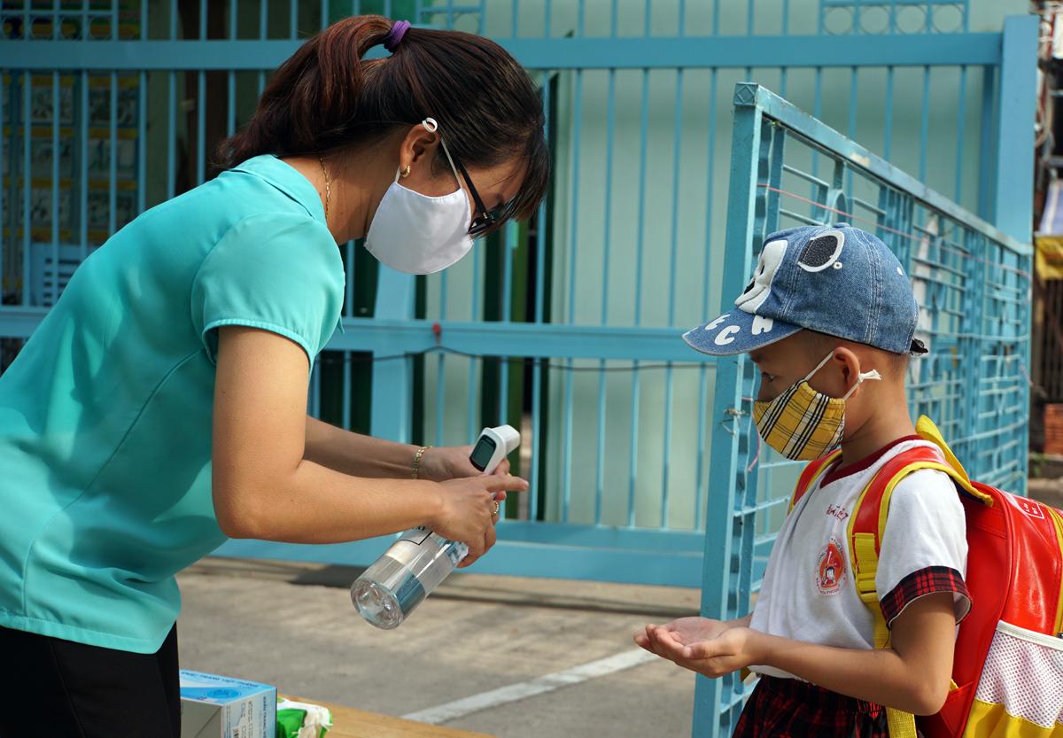 Nhân viên trường Mầm non Hoa Phượng Đỏ, quận Gò Vấp, TP HCM đo thân nhiệt, rửa tay cho học sinh trong ngày đầu trở mở cửa sau Covid-19, sáng 18/5. Ảnh: Mạnh Tùng.