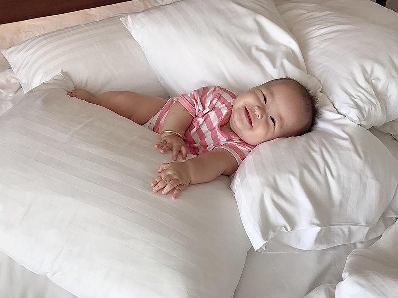 Con cười tươi lúc được nằm lên giường sau chuyến đi dài.