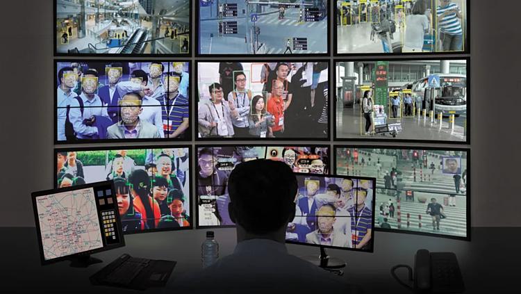 Một nhân viên Trung Quốc theo dõi an ninh qua camera giám sát và nhận diện gương mặt. Ảnh: Reuters.