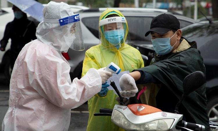 Tình nguyện viên mặc đồ bảo hộ đang đo thân nhiệt cho một người đàn ông tại lối vào khu dân cư ở thành phố Cát Lâm, tỉnh Cát Lâm, Trung Quốc hôm 22/5. Ảnh: Reuters.