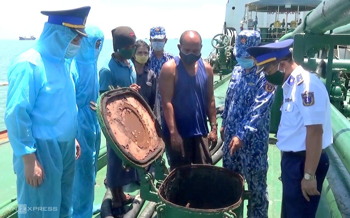 Thuyền trưởng (thứ 3 từ phải) mở nắp hầm chứa dầu tàu để cảnh sát biển kiểm tra. Ảnh: Đức Định.