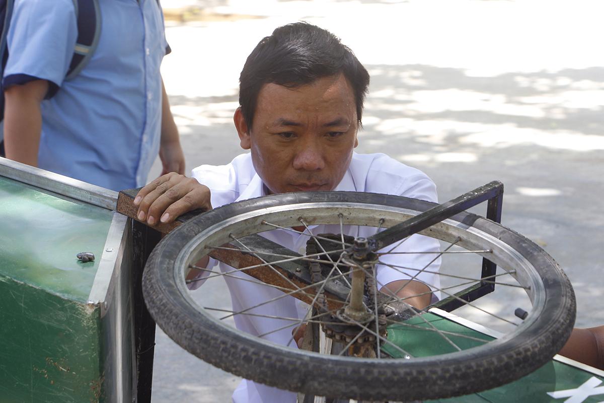 Thầy Phan Hữu Tùng chỉnh sửa xe quét rác. Ảnh: Võ Thạnh