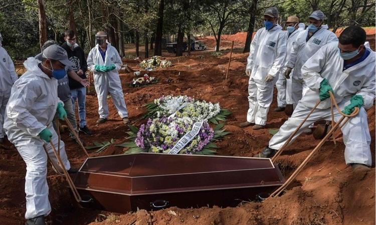Công nhân mặc đồ bảo hộ chôn cất nạn nhân Covid-19 tại một nghĩa trang ở ngoại ô Sao Paulo, Brazil hôm 20/5. Ảnh: AFP.