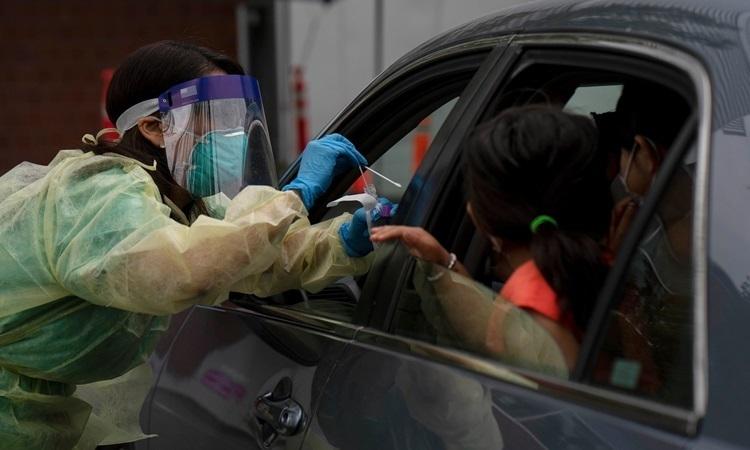 Nhân viên y tế Mỹ lấy mẫu xét nghiệm nCoV cho những người trong xe tại bang Oregon. Ảnh: NY Times.