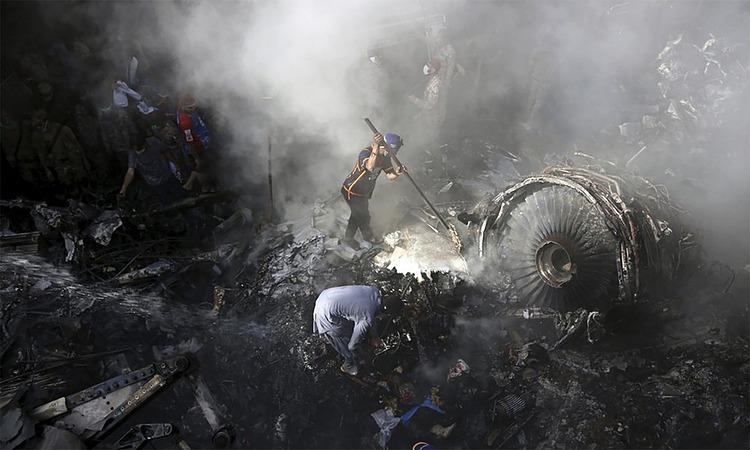 Nhân viên cứu hộ dùng xà beng bẩy động cơ máy bay để tìm kiếm nạn nhân bên dưới đống đổ nát hôm 22/5. Ảnh: Reuters.