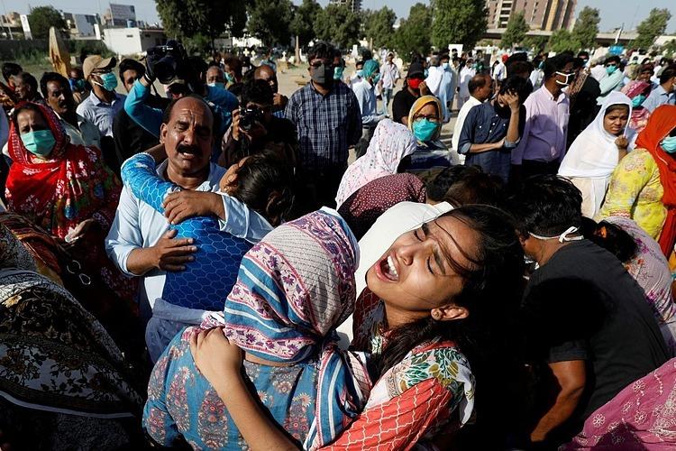 Người nhà nạn nhân thiệt mạng trong vụ rơi máy bay ở Karachi khóc thương người thân trong đám tang hôm 25/5. Ảnh: Reuters.