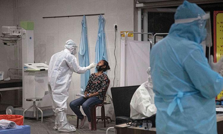 Nhân viên y tế lấy mẫu xét nghiệm nCoV tại thành phốGauhati, bang Assam, hôm 17/5. Ảnh: AP.