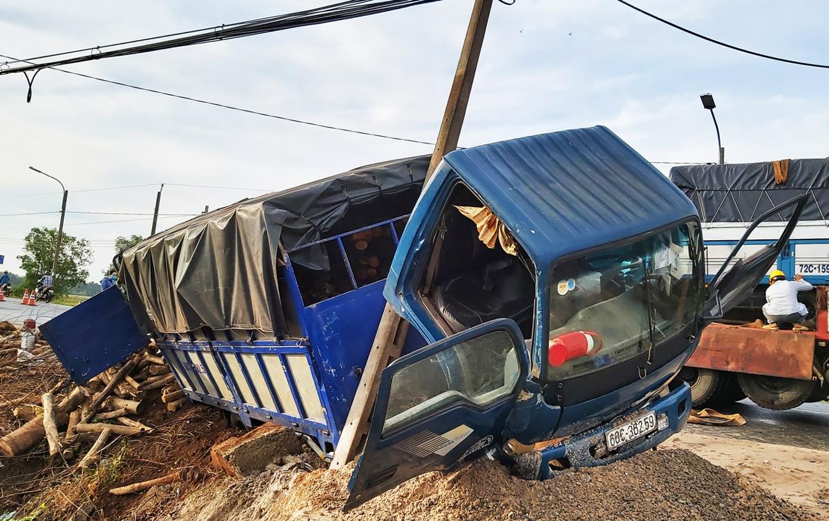 Xe chở củi được cột điện ven đường chặn lại nên không bị lật. Ảnh: Hắc Minh.