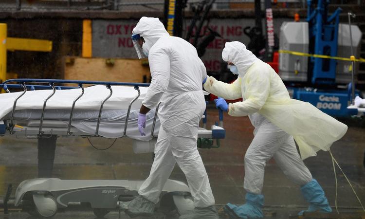 Nhân viên y tế chuyển xác bệnh nhân tới xe tải đông lạnh ở Bệnh việnBrooklyn, thành phố New York, hôm 9/4. Ảnh: AFP.