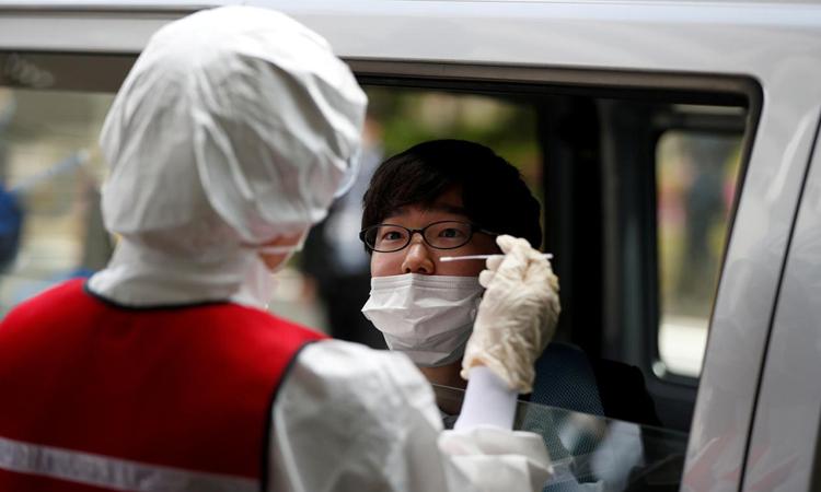 Nhân viên y tế lấy mẫu xét nghiệm nCoV trên xe tạiEdogawa, thủ đô Tokyo, hôm 22/4. Ảnh: Reuters.