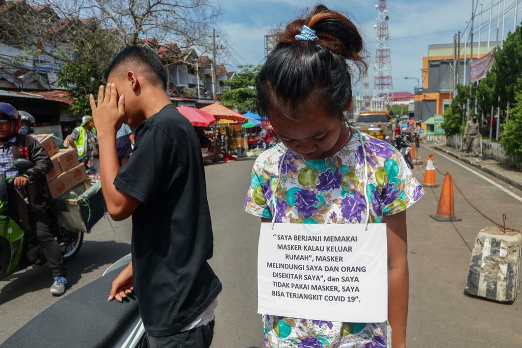 Một bé gái bị phạt đeo bảng Tôi hứa sẽ mang khẩu trang và chụp ảnh đăng lên mạng tại Bengkulu hôm 13/5. Ảnh: AFP