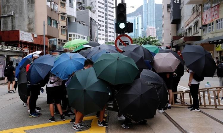 Người biểu tình phản đối dự luật an ninh Hong Kong dùng ô tạo thành rào chắn trên đường phố của đặc khu ngày 24/5. Ảnh: Reuters.