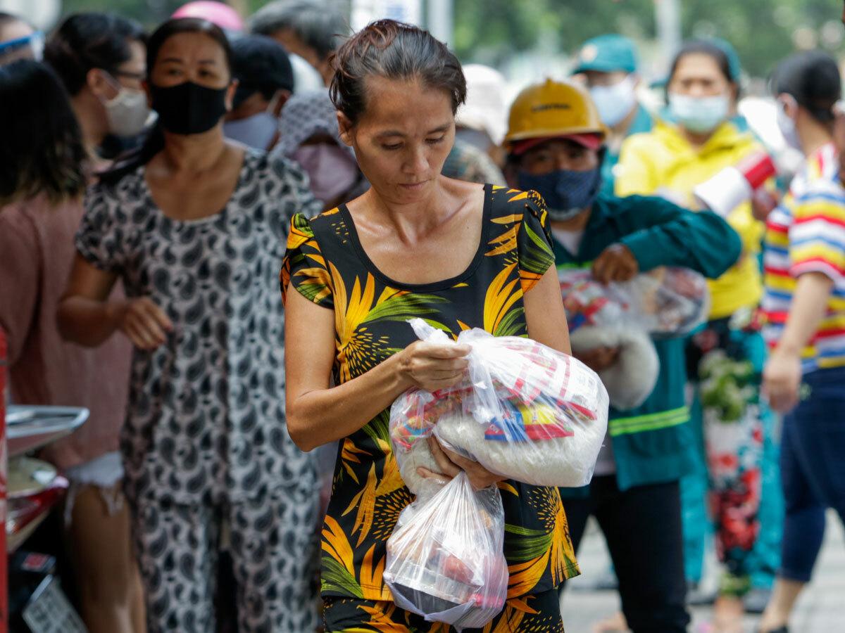 Người lao động tự do nhận cơm từ thiện trên đường Trần Hưng Đạo, quận 1, trong những ngày mất thu nhập vì Covid-19, ngày 2/4. Ảnh: Nguyệt Nhi.