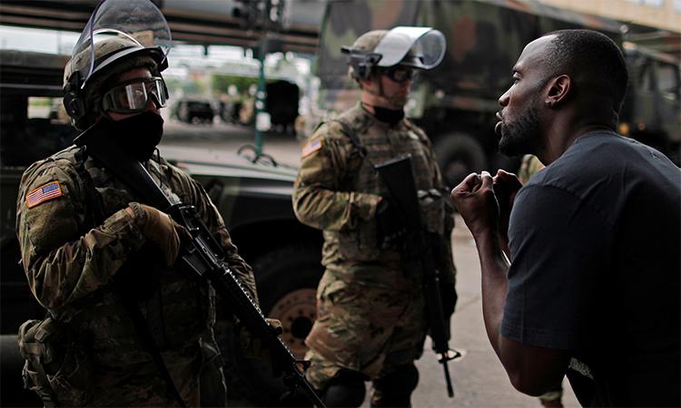 Một người biểu tình tỏ thái độ phản đối trước mặt binh sĩ Vệ binh Quốc gia gác trên đường phố Minneapolis, bang Minnesota, Mỹ, ngày 29/5. Ảnh: Reuters.