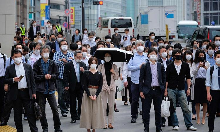 Người dân đeo khẩu trang đứng chờ sang đường ở thủ đô Tokyo, Nhật Bản. Ảnh: AFP.