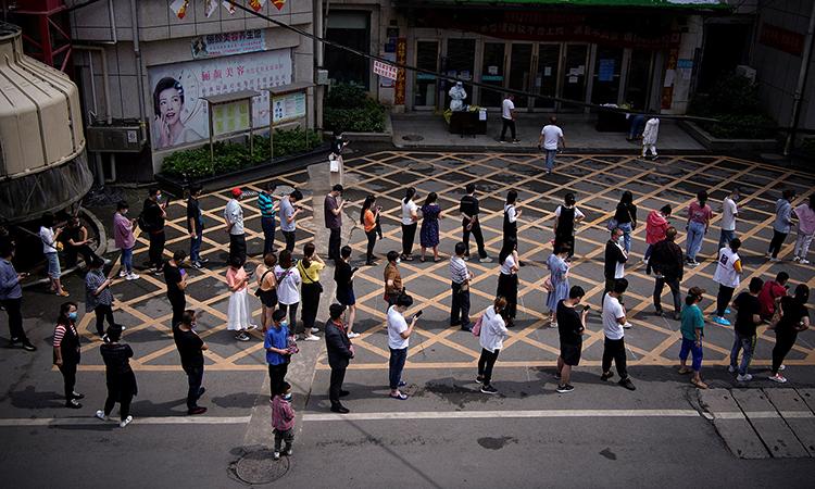 Người dân xếp hàng chờ lấy mẫu xét nghiệm nCoV trước một chung cư ở thành phố Vũ Hán, Trung Quốc, tháng này. Ảnh: Reuters.