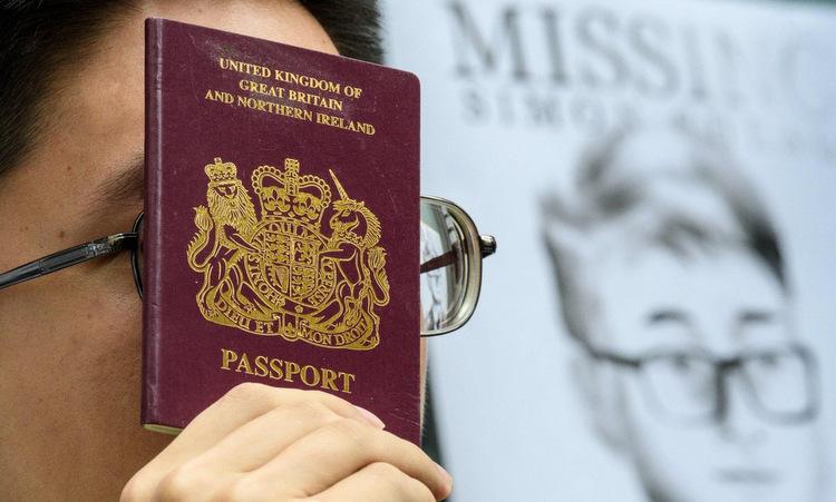 Người biểu tình cầm hộ chiếu Anh tuần hành ngoài lãnh sự quán Anh tại Hong Kong hồi năm 2019. Ảnh: AFP.
