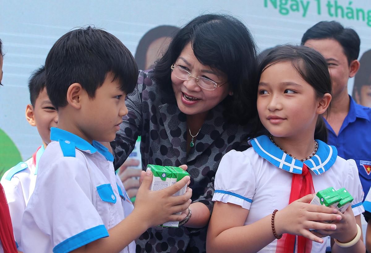 Phó chủ tịch nước Đặng Ngọc Thịnh tặng sữa cho học sinh sáng 1/6. Ảnh: Đắc Thành.
