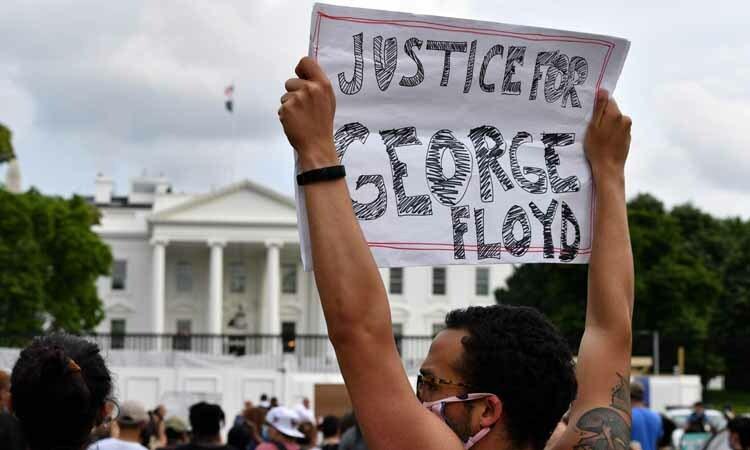 Một người biểu tình giơ tờ giấy có dòng chữ công lý cho George Floyd bên ngoài Nhà Trắng hôm 29/5. Ảnh: AFP.