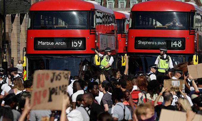 Cảnh sát giám sát biểu tình bên ngoài tòa nhà quốc hội Anh, hôm 31/5. Ảnh: AP.