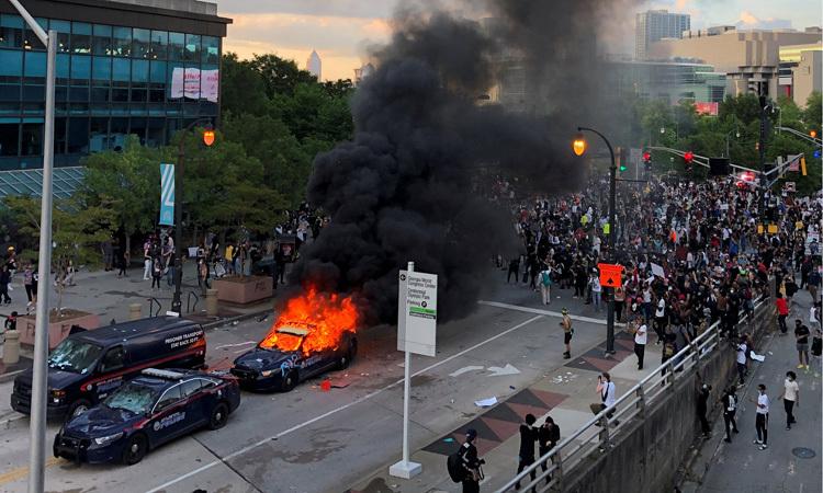Xe cảnh sát bốc cháy trong cuộc biểu tình tại thành phố Atlanta, bang Georgia, Mỹ hôm 29/5. Ảnh: NY Times.