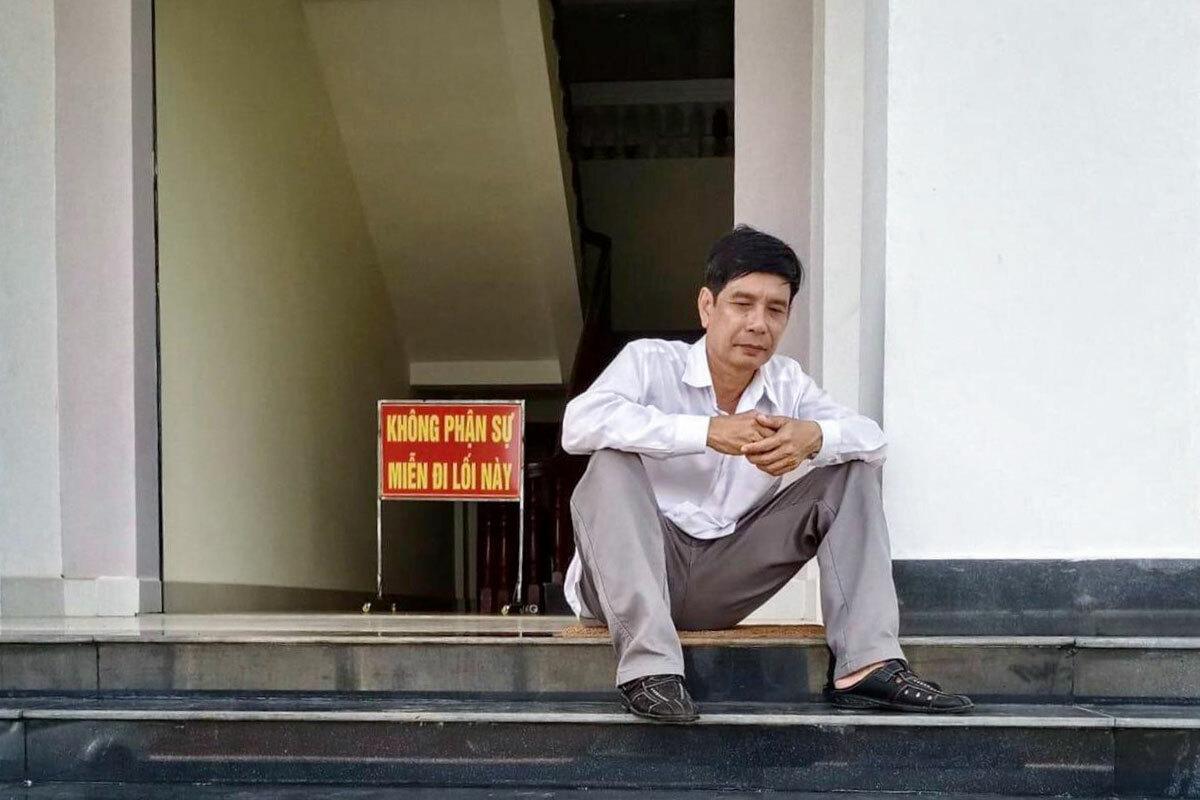 Ông Phước ngồi tại sân tòa trước lúc tuyên án sáng 29/5. Ảnh: Luật sư cung cấp.