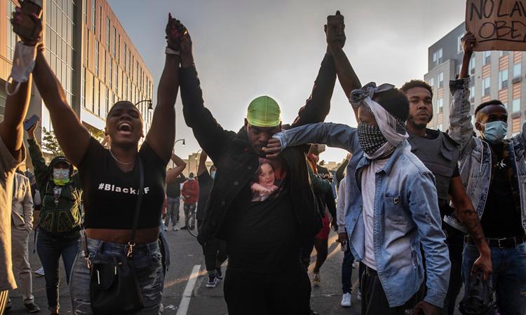 Người biểu tình lấy tay lau nước mắt cho nhau ởLake Street, thành phố Minneapolis, cuối tuần qua. Ảnh: NYTimes.