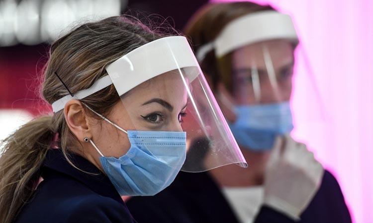 Hai nhân viên bán hàng tại một trung tâm thương mại ở Moskva, Nga, đeo khẩu trang và kính chắn phòng nCoV hôm 1/6. Ảnh: AFP.