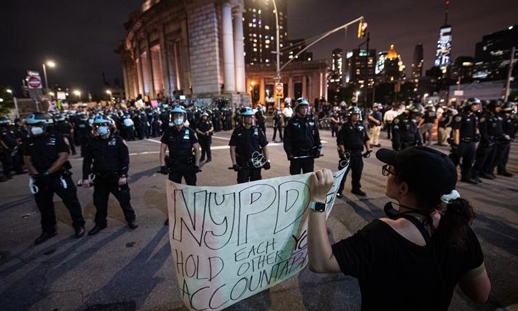 Người biểu tình đối mặt lực lượng an ninh ở New York trong thời gian áp lệnh giới nghiêm tối 2/6. Ảnh: Reuters.